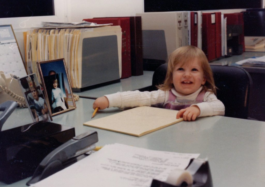 Young Julia sitting at her father's desk, ready to work.